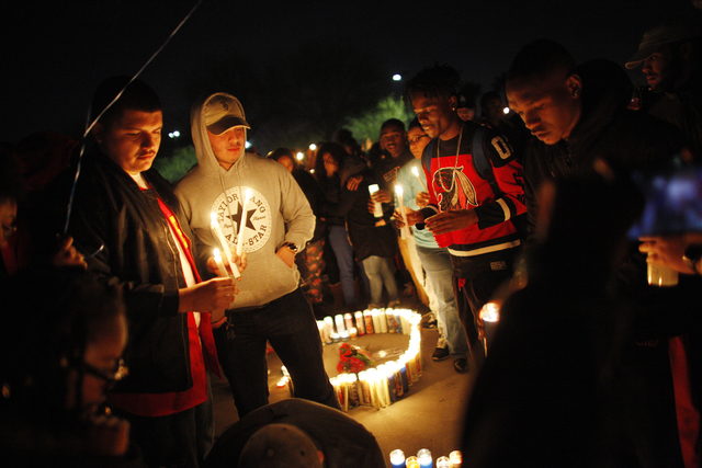 """A crowd places candles to form """"RN 20"""" at a vigil in honor of Richard Nelson on Sunday, Jan. 15, 2017, at Chaparral High School in Las Vegas. Nelson was shot and killed Saturday  ..."""