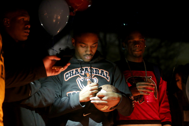 Seite Wyehe, 19, signs a football at a vigil in honor of Richard Nelson on Sunday, Jan. 15, 2017, at Chaparral High School in Las Vegas. Nelson was shot and killed Saturday night in front of his h ...