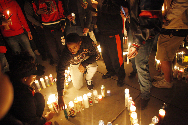 Seite Wyehe, 19, lights a candle at a vigil in honor of Richard Nelson on Sunday, Jan. 15, 2017, at Chaparral High School in Las Vegas. Nelson was shot and killed Saturday night in front of his ho ...