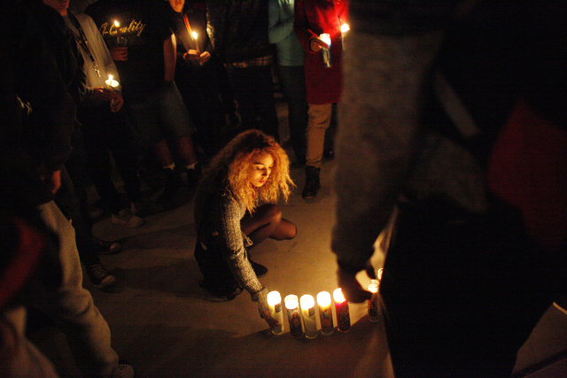 A girl lights sets down a candle at a vigil in honor of Richard Nelson on Sunday, Jan. 15, 2017, at Chaparral High School in Las Vegas. Nelson was shot and killed Saturday night in front of his ho ...