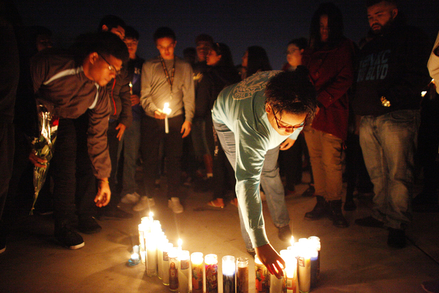 Keyara McKinsey lights a candle at a vigil in honor of Richard Nelson on Sunday, Jan. 15, 2017, at Chaparral High School in Las Vegas. Nelson was shot and killed Saturday night in front of his hom ...