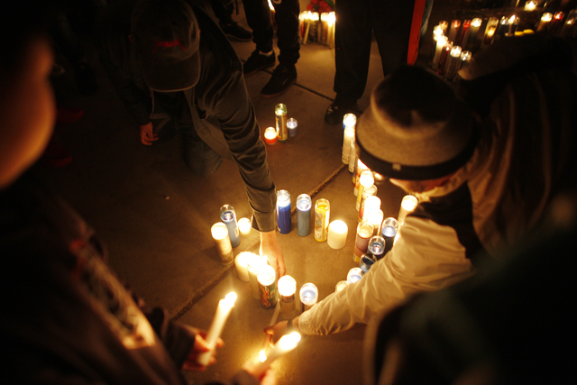 A crowd sets down candles at a vigil in honor of Richard Nelson on Sunday, Jan. 15, 2017, at Chaparral High School in Las Vegas. Nelson was shot and killed Saturday night in front of his home. (Ra ...