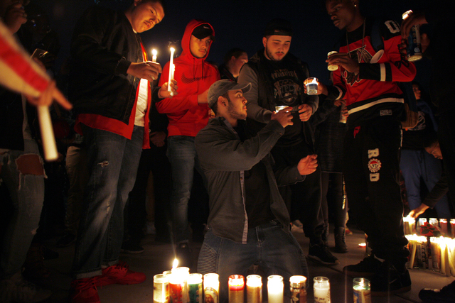 Chris Salazar prepares do set down a candle at a vigil in honor of Richard Nelson on Sunday, Jan. 15, 2017, at Chaparral High School in Las Vegas. Nelson was shot and killed Saturday night in fron ...