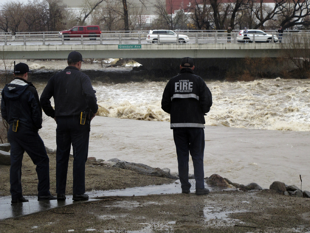 Sparks firefighters monitor the rising Truckee River, Sunday, Jan. 8, 2017, where it runs near the Grand Sierra hotel-casino along a line that divides the cities of Reno and Sparks, Nev. More than ...