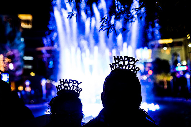Santos and Maria Hernandez enjoy the fountain outside the Wynn hotel-casino on the Strip on New Year's Eve in Las Vegas. (Benjamin Hager/Las Vegas Review-Journal)