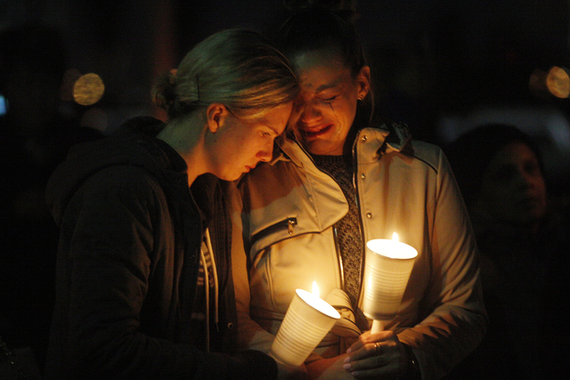 Two women pray at a candlelight vigil to honor North Las Vegas Police Detective Chad Parque in front of the North Las Vegas Justice Court on Sunday, Jan. 8, 2017, in Las Vegas. (Rachel Aston/Las V ...