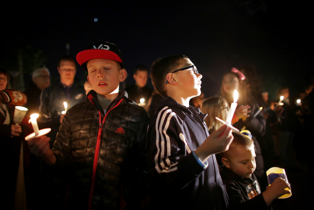 Gabriel Manteufel, 9, from left, Mason Feeley, 7, and his little brother Brooks Feeley, 3, pray at a candlelight vigil to honor North Las Vegas Police Detective Chad Parque in front of the North L ...