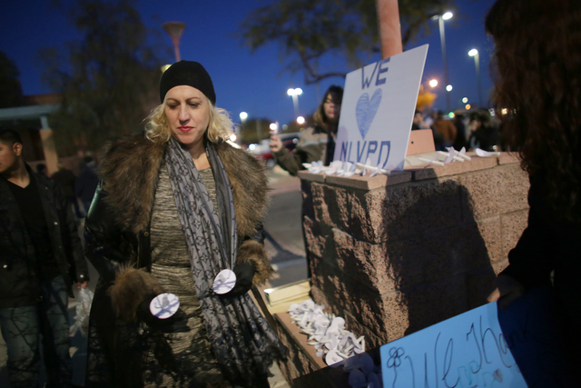 Linda Burns picks up candles at a candlelight vigil to honor North Las Vegas Police Detective Chad Parque in front of the North Las Vegas Justice Court on Sunday, Jan. 8, 2017, in Las Vegas. (Rach ...