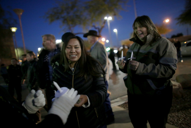 Candice Herrara, left, and Sharon Rodriguez hand out candles at a candlelight vigil to honor North Las Vegas Police Detective Chad Parque in front of the North Las Vegas Justice Court on Sunday, J ...