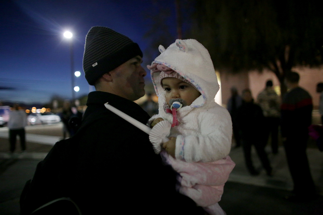 Ray Cantu holds his daughter Samantha Cantu, 1, at a candlelight vigil to honor North Las Vegas Police Detective Chad Parque in front of the North Las Vegas Justice Court on Sunday, Jan. 8, 2017,  ...