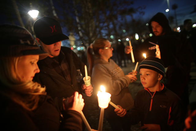 Braydon Allen, 9, has his candle lit by Cece Stanton, next to her husband Jason Stanton at a candlelight vigil to honor North Las Vegas Police Detective Chad Parque in front of the North Las Vegas ...