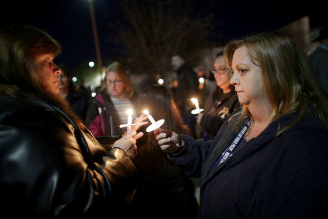 Teresa Ryan lights the candle of Jennifer Whitley at a candlelight vigil to honor North Las Vegas Police Detective Chad Parque in front of the North Las Vegas Justice Court on Sunday, Jan. 8, 2017 ...