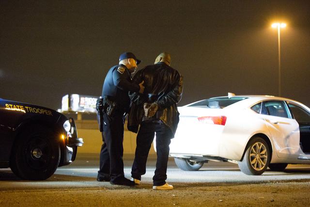 Nevada Highway Patrol trooper Ervin Raab, left, arrests a DUI suspect near the Spaghetti Bowl on Dec. 31, 2016. (Elizabeth Brumley/Las Vegas Review-Journal) @EliPagePhoto