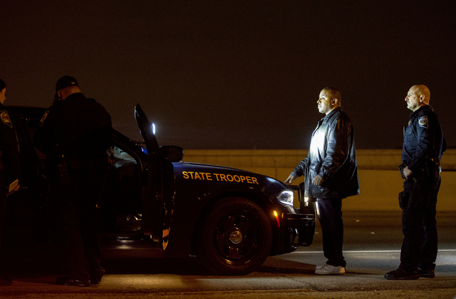 Nevada Highway Patrol troopers Ervin Raab, left, and John Morris, right, conduct a field sobriety test for a DUI suspect near the Spaghetti Bowl on Dec. 31, 2016. (Elizabeth Brumley/Las Vegas Revi ...