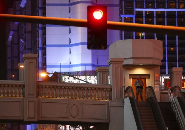 A Las Vegas police officer guards a pedestrian bridge as New Year's Eve revelers gather on the Las Vegas Strip on Saturday, Dec. 31, 2016. (Chase Stevens/Las Vegas Review-Journal) @csstevensphoto