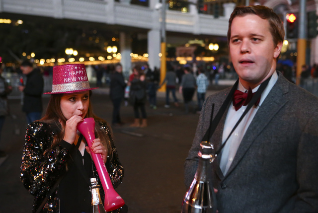Taylor Davis of Chicago, left, sips on her drink as Johnny Bretz looks on while New Year's Eve revelers gather on the Las Vegas Strip on Saturday, Dec. 31, 2016. (Chase Stevens/Las Vegas Review-Jo ...