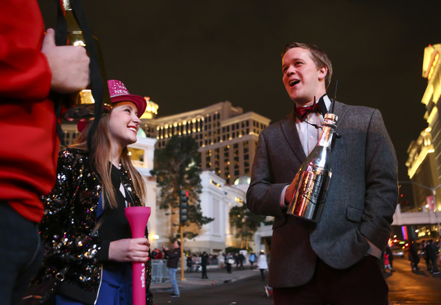 Johnny Bretz, right, of Indianapolis talks as Taylor Davis of Chicago looks on while New Year's Eve revelers gather on the Las Vegas Strip on Saturday, Dec. 31, 2016. (Chase Stevens/Las Vegas Revi ...