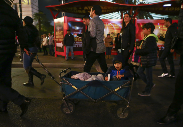 A man who declined to give his name pulls a child on a cart as New Year's Eve revelers gather on the Las Vegas Strip on Saturday, Dec. 31, 2016. (Chase Stevens/Las Vegas Review-Journal) @csstevens ...