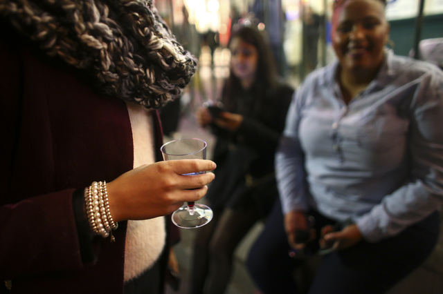 Anastasiia, last name declined, of Ukraine holds a plastic wine glass as New Year's Eve revelers gather on the Las Vegas Strip on Saturday, Dec. 31, 2016. (Chase Stevens/Las Vegas Review-Journal)  ...