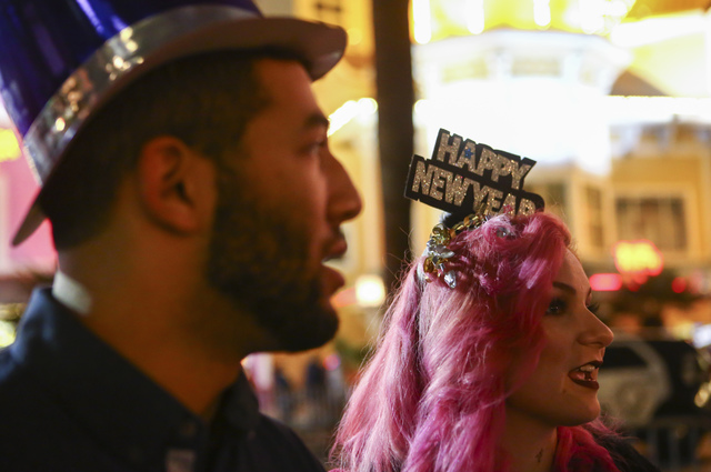 Twenty-year-old Joshua Shaver, left, and Loretta Strickland, 19, talk as New Year's Eve revelers gather on the Las Vegas Strip on Saturday, Dec. 31, 2016. (Chase Stevens/Las Vegas Review-Journal)  ...