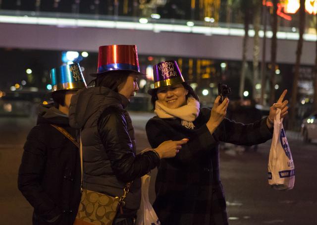 New Year's Eve revelers from right, Tomomi, Motoko and Hiro of Japan take pictures of the Las Vegas Strip on Saturday, Dec. 31, 2016. (Miranda Alam/Las Vegas Review-Journal) miranda.alam