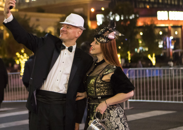 New Year's Eve revelers Kevin DeFord, left, and his wife Jody DeFord take a selfie on the Las Vegas Strip on Saturday, Dec. 31, 2016. (Miranda Alam/Las Vegas Review-Journal) miranda.alam