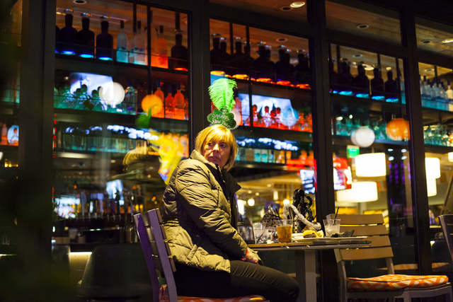 A woman watches New Year's Eve revelers from Tom's Urban on the Las Vegas Strip on Saturday, Dec. 31, 2016. (Miranda Alam/Las Vegas Review-Journal) miranda.alam