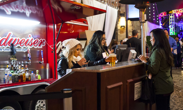 A woman buys beer outside of the New York-New York hotel-casino on the Las Vegas Strip on Saturday, Dec. 31, 2016. (Miranda Alam/Las Vegas Review-Journal) miranda.alam