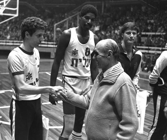 Moshe Dayan shakes hands with Macabbi Tel Aviv basketball player Motti Aroesti as Aulci Perry and Miky Berkovitz look on at the Yad Eliyahi Stadium.