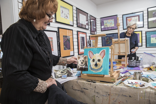 Instructor Georgia Lawson, left, compares a photo of Sweet Pea with a completed painting by Judi Moreo during a pet portrait class on Thursday at City Lights Gallery. Students use a photo of their ...