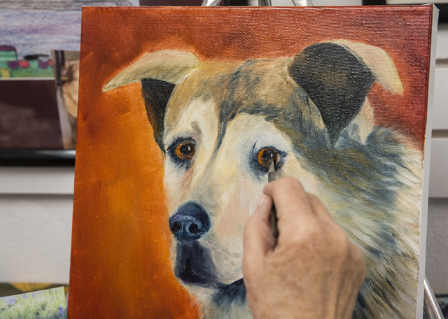 "Lucia Sullivan touches up the eye on a painting of her Siberian husky-German shepherd mix during a pet portrait workshop. When painting their pets, the students begin with the eyes because ""you wa ..."