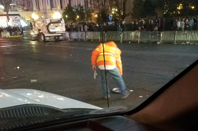 Clark County Department of Public Works maintenance supervisor Don Ficklen picks up a hub cap off of Las Vegas Boulevard during post-New Year's cleanup on the Las Vegas Strip, Sunday, Jan. 1, 2017 ...