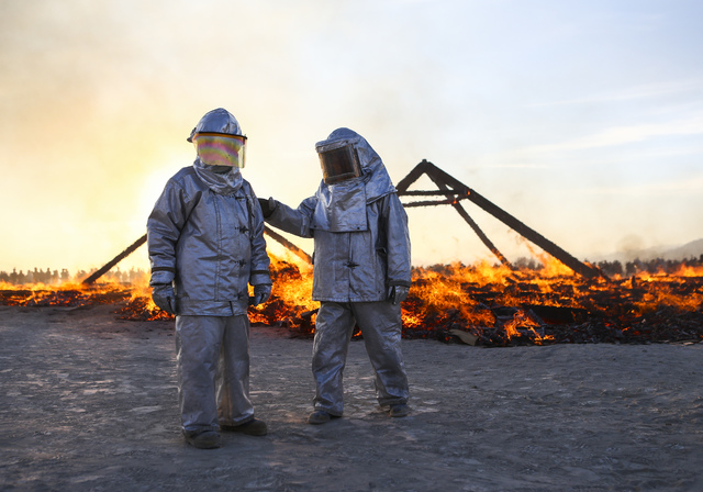 Fire safety workers stand as the Catacomb of Veils art installation burns at sunrise during Burning Man at the Black Rock Desert north of Reno on Friday, Sept. 2, 2016. Chase Stevens/Las Vegas Rev ...