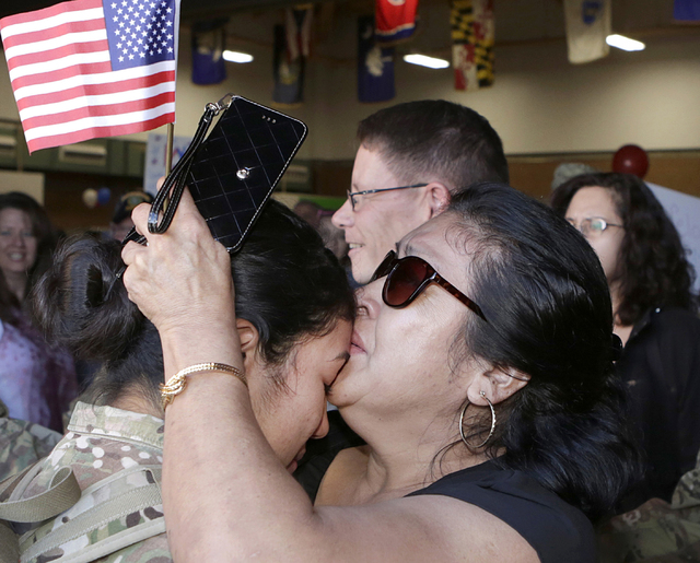 Rosemary Lopez, right, embraces her daughter Spc. Diana Lopez during a welcome home ceremony Wednesday, Nov. 9, 2016, in Las Vegas. About 150 soldiers from the Nevada Army National Guard reunite w ...