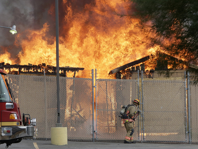 A Las Vegas firefighter tries to unlock a gate as flames burn through a boarded-up building at 1614 E. Lake Mead Blvd. in North Las Vegas on Tuesday, Sept. 20, 2016. (Bizuayehu Tesfaye/Las Vegas R ...