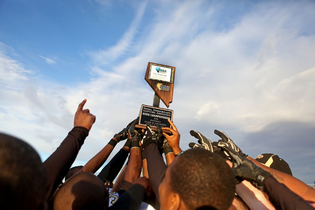 Spring Mountain Eagles hold their trophy together after they winning the class 1A state football final neutral playoff game against Pahranagat Valley at Clark High School in Las Vegas, Saturday, N ...