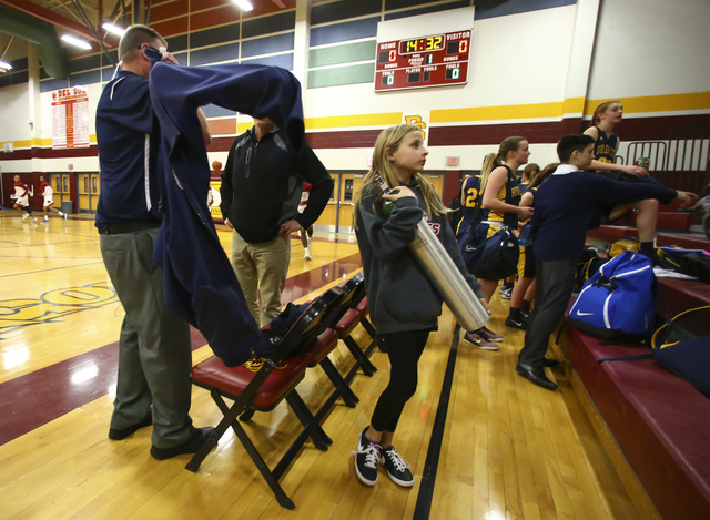 Alexis Farrar, 11, holds an oxygen tank belonging to her mother's fiancé, Paul Dosch, the coach of the Boulder City girls basketball team, after a game at Del Sol High School in Las Vegas on Tues ...