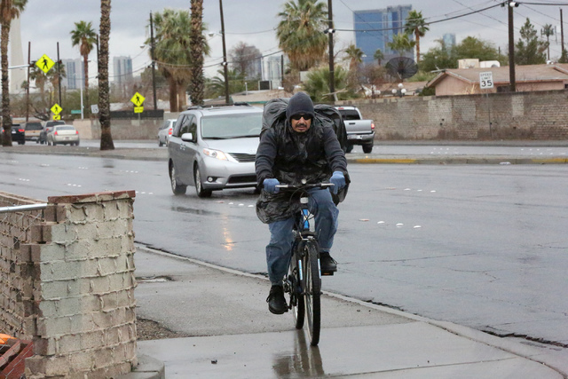 Javier Gonzales makes his way down Martin Luther King Boulevard on his bicycle on a rainy Friday, Jan. 13, 2017. (Michael Quine/Las Vegas Review-Journal) @Vegas88s