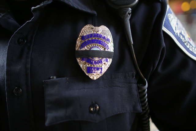 North Las Vegas Officer Teodoro Mendez Jr. wears a black band on his badge to commemorate the death of North Las Vegas police detective Chad Parque at the All County Law Enforcement Agencies Recru ...