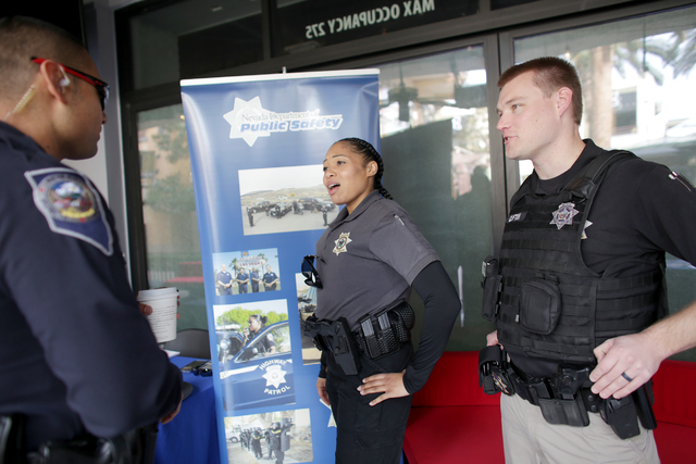 Nevada Highway Patrol trooper Bernard Abarca, left, Department of Public Safety Officer M. Triplett and Parole and Probation Officer C. Clifton talk at the All County Law Enforcement Agencies Recr ...