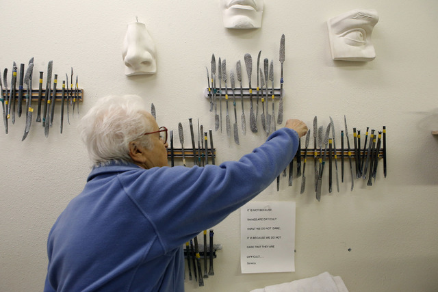 Sculptor Sharon Gainsburg, 74, reaches for a stone carving tool at her studio. She moved into the studio on West Oakey Boulevard about three years ago from the Arts District and now hosts students ...