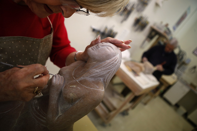 Anne Furno, a student in Sharon Gainsburg's stone carving class, puts the final touches on her carving of a kneeling woman. Next, she will wet sand the piece to help achieve a smooth and shiny fin ...