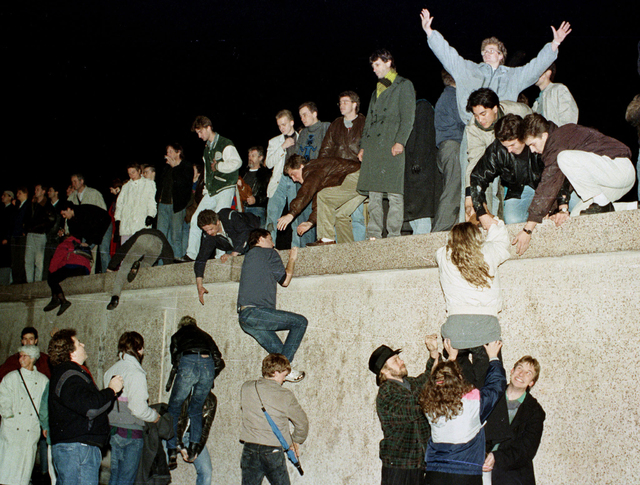 East German citizens climb the Berlin wall at the Brandenburg Gate as they celebrate the opening of the East German border in this November 10, 1989 file photo. The 10th anniversary of the &qu ...