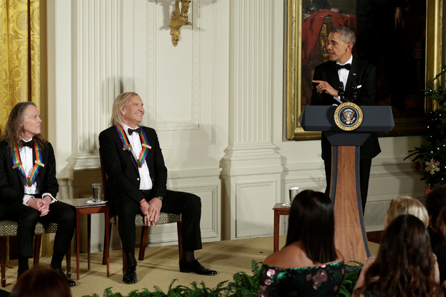 U.S. President Barack Obama (R) delivers remarks next to members of rock band Eagles Joe Walsh and Timothy B. Schmit (L) at the Kennedy Center Honors Reception at the White House in Washington, U. ...