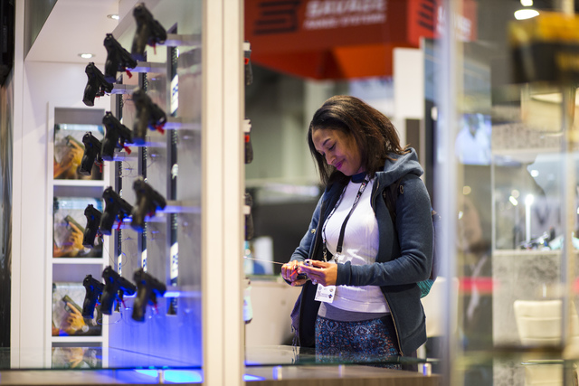 Sherrone McCareins of Texas looks at a Walther PK380 during SHOT Show at the Sands Expo and Convention Center in Las Vegas on Thursday, Jan. 19, 2017. (Chase Stevens/Las Vegas Review-Journal) @css ...
