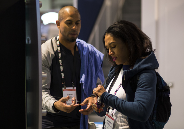 Sherrone McCareins of Texas looks at a Walther CCP as her husband, former NFL player Justin McCareins, during SHOT Show at the Sands Expo and Convention Center in Las Vegas on Thursday, Jan. 19, 2 ...