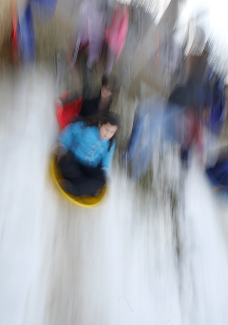 Kids slide down a hill at the Arbors Tennis and Play Park on Saturday, Jan. 28, 2017, in Las Vegas. The park offered sledding and other activities to the visitors. (Christian K. Lee/Las Vegas Revi ...
