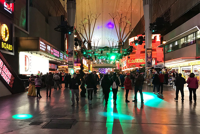 New Year's Eve crowds trickle in to Fremont Street after the gates open. (Amelia Pak-Harvey/Las Vegas Review-Journal)