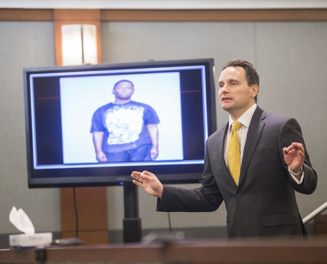 Defense attorney Josh Tomsheck addresses the jury with a photo of key witness Jeremiah Merriweather on display during closing arguments in the death penalty murder trial of Brandy Stutzman on Frid ...