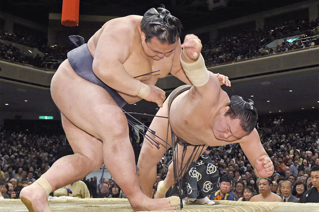 Ozeki Kisenosato, left, pushes Mongolian grand champion Hakuho out of the ring during the final day bout of the New Year Grand Sumo Tournament at Ryogoku Kokugikan sumo hall in Tokyo Sunday, Jan.  ...